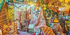 SHIRAZ, IRAN - OCTOBER 12, 2017: Scenic carpet stall with colored kilims and rugs, covered with patterns, neighbors with antique stall with different souvenirs and jewelries, Vakil Bazaar, on October 12 in Shiraz.